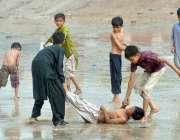ملتان: بچے بارش کے دوران کھیل کود میں مصروف ہے۔