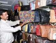 لاہور: ایک دکاندار فروخت کے لیے بیگ سجارہا ہے۔