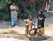 لاہور: گرمی کی شدت کم کرنے کے لیے بچے ہینڈ پمپ کے پانی سے نہا رہے ہیں۔