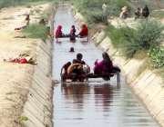 فیصل آباد: خانہ بدوش فیملی گرمی کی شدت سے بچنے کے لیے نہر کے اندر چارپائی ..