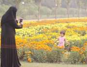 لاہور: جیلانی پارک میں ایک خاتون اپنی بچی کی پھولوں کے پاس تصویر بنار ..