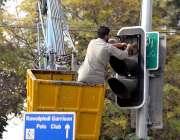 راولپنڈی: واپڈا کا اہلکار ٹریفک سگنل مرمت کررہا ہے۔