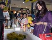 اسلام آباد: ایک خاتون مینگو فیسٹیول میں رکھے گئے آم پسند کر رہی ہے۔