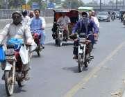 لاہور: موٹر سائیکل سوار گرمی کی شدت سے بچنے کے لیے منہ پر رومال لپیٹے ..