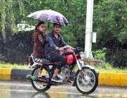 اسلام آباد: وفاقی دارالحکومت میں ہونیوالی بارش سے بچنے کے لیے موٹرسائیکل ..