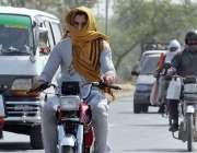 راولپنڈی: موٹر سائیکل سوار دھوپ اور گرمی کی شدت سے بچنے کے لیے منہ پر ..
