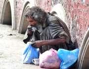 لاہور: مخبوط الحواس شخص ایک موریہ پل کے قریب بیٹھا کھانا کھارہا ہے۔