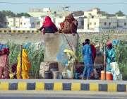 حیدر آباد: خانہ بدوش خواتین اور بچے پینے کے لیے صاف پانی بوتلوں میں ..