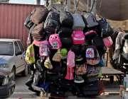 راولپنڈی: ہفتہ وار جمعہ بازار میں ایک محنت کش نے بجلی کے پول پر بیگ فروخت ..