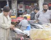 لاہور: مچھلی منڈی میں ایک کاریگر مچھلی کی صفائی میں مصروف ہے۔