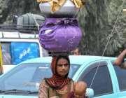 ملتان: خانہ بدوش خاتون پینے کے لیے صاف پانی برتنوں میں بھر کر لیجا رہی ..