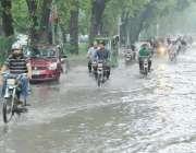 لاہور: شہری موسلا دھار بارش کے بعد مال روڈ پر جمع پانی سے گزر رہے ہیں۔