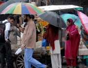 راولپنڈی: راجہ بازار میں خواتین چھتری تھامے بارش رکنے کا انتظار کر ..