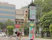 لاہور: لبرٹی چوک میں ایک کاریگر الیکٹرک اشتہاری بورڈ ٹھیک کر رہا ہے۔