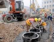 لاہور: مزدور جی پی او چوک میں جاری اورنج لائن میٹرو ٹرین منصوبے پر کام ..
