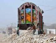 ملتان: مزدور ٹرک سے پتھر اتارنے میں مصروف ہے۔