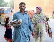 لاہور: بادشاہی مسجد کے باہر ایک شخص کچی گری فروخت کررہا ہے۔