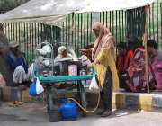 ملتان: ایک محنت کش خاتون خاتون سڑک کنارے چائے کا سٹال لگائے بیٹھی ہے۔