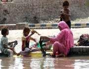 ملتان: خانہ بدوش خاتون اپنے بچوں کے ہمراہ نہر کنارے بیٹھی کپڑے دھو رہی ..