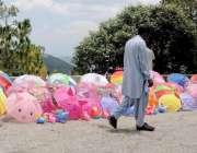 مری: سڑک کنارے ایک محنت کش نے دھوپ سے بچاؤ کے لیے چھتریاں فروخت کے لیے ..