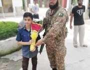 لاہور: عام انتخابات 2018  پولنگ اسٹیشن پر تعینات فوجی جوان کو ایک بچہ ..
