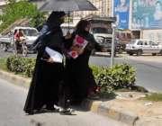 راولپنڈی: خواتین دھوپ سے بچنے کے لیے چھتری تھامے روڈ کراس کر رہی ہیں۔