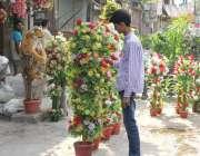 لاہور: شاہ عالم مارکیٹ میں ایک نوجوان مصنوعی پھول فروخت کرنے کے لیے ..