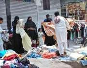 ملتان: خواتین سڑک کنارے لگے سٹال سے کپڑے پسند کر رہی ہیں۔