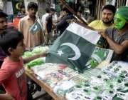 لاہور: اردو بازار میں ایک بچہ قومی پرچم خرید رہا ہے۔