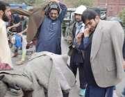 لاہور: موسم سرما کی آمد پر ایک شہری لنڈا بازار میں پٹھان سے کوٹ خرید ..