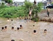 اسلام آباد: بارش کے جمع پانی میں بچے نہا رہے ہیں۔