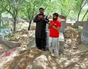 فیصل آباد: محرم الحرام کے پیش نظر دو افراد اپنے پیاروں کی قبر پر فاتحہ ..