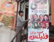لاہور: رائل پارک میں ایک شخص فلیکسز پرنٹ کروانے کے لیے بورل پر آویزاں ..