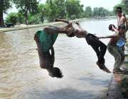 ملتان: نوجوان گرمی کی شدت کم کرنے کے لیے نہر میں نہا رہے ہیں۔