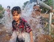 سرگودھا: ایک بچہ گرمی کی شدت کم کرنے کے لیے ٹیوب ویل کے پانی سے نہا رہا ..