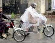 لاہور: شہر میں ہونیوالی بارش کے دوران ایک موٹر سائیکل سوارپلاسٹک اوڑھے ..