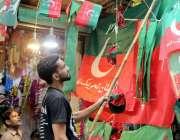لاہور: رائل پارک میں ایک دکاندار سیاسی جماعت کے پرچم فروخت کرنے کے لیے ..