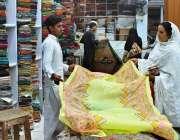 ملتان: عید کی تیاریوں میں مصروف خواتین کپڑے پسند کر رہی ہیں۔