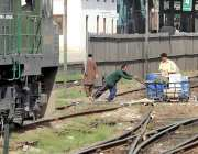 راولپنڈی: محنت کش ہتھ ریڑھی پر پانی کی بوتلیں رکھے ریلوے ٹریک کراس کر ..