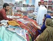 ملتان: عید کی خریداری میں مصروف خواتین کپڑے پسند کر رہی ہیں۔