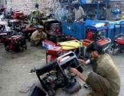 پشاور: مکینک اپنی ورکشاپ میں جنریٹر مرمت کر رہے ہیں۔