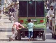 لاہور: دو کمسن بچے خراب رکشے کے دھکہ لگا رہے ہیں۔