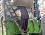 فیصل آباد: مزدور ٹرک پر ردی وغیرہ لوڈ کرنے میں مصروف ہے۔