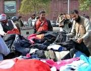 لاہور: شہری سڑک کنارے لگے سٹال سے استعمال شدہ گرم کپڑے خرید رہے ہیں۔