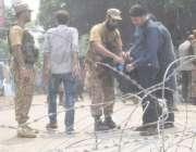 لاہور: پاک فوج کا جوان پولنگ کا سامان لینے کے لیے آنے والے پریزائیڈنگ ..