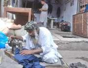لاہور: ایک درزی بجلی کی لوڈ شیڈنگ کے باعث دکان کے باہر بیٹھا کھڑے سلائی ..
