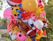 لاڑکانہ: ایک محنت کش غبارہ نما کھلونے فروخت کررہا ہے۔