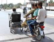 ملتان: موٹر سائیکل سوار معذور شخص کی وہیل چیئر کودھکا لگا رہے ہیں۔
