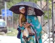 راولپنڈی: ایک خاتون اپنے بچے کے ہمراہ دھوپ کی شدت سے بچنے کے لیے چھتری ..