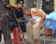 راولپنڈی: نوجوان گرمی کی شدت کم کرنے کے لیے ایک معمر شخص کے سر پر پانی ..